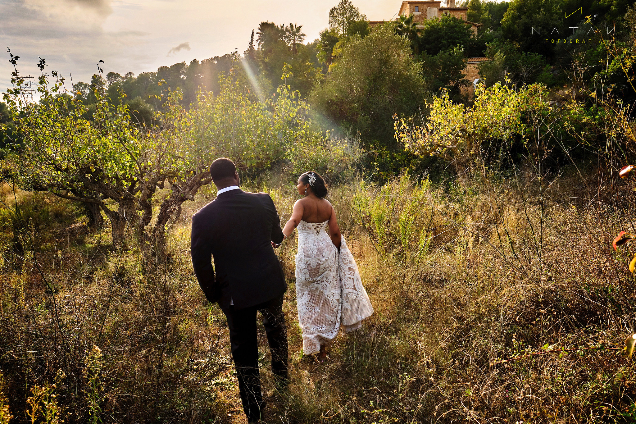 bride and groom walking in the field,  wedding day in Sitges mediterranean light